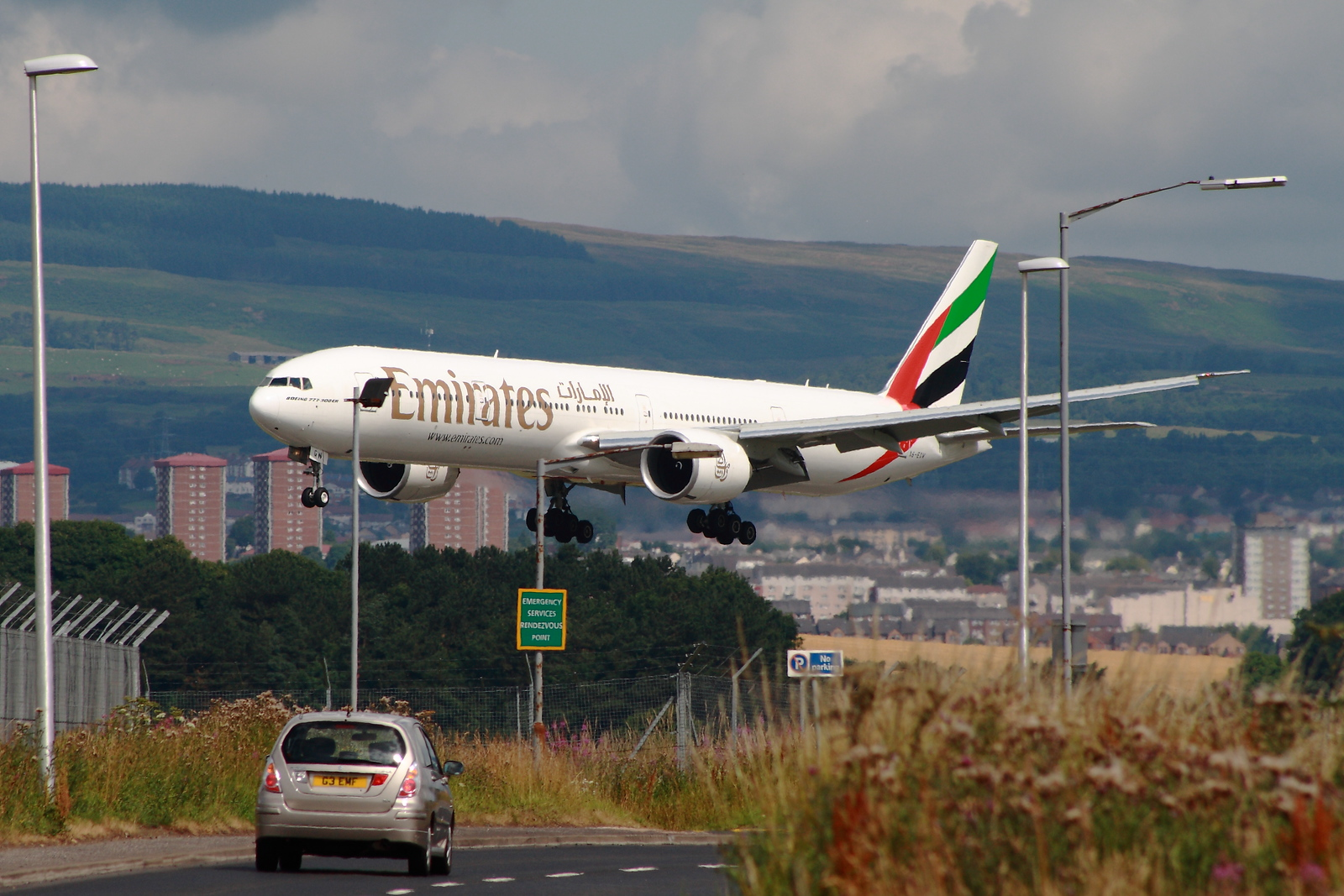 An Emirates Boeing 777-31H/ER (A6-EGP) on approach to Glasgow Airport. The car in the foreground gives an idea of just how big the B777 is.