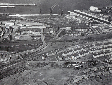 This view of Inchgreen shows the new dry dock and cranes under construction. The dry dock was built on the site of the Gas Works, which had a branch line serve it which joined the Princes Pier line at Cartsburn Junction. The embankment for the line if in the centre of shot and the track had been lifted when this picture was taken. Next to the cranes in the picture is the mineral sidings that served the old Gas Works, the Great Harbour and James Watt Dock. To the left of the picture if the mineral sidings at Ladyburn and Greenock (Ladyburn) Shed, which closed in 1966 and is now covered by housing.