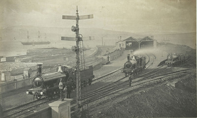 The station at Princes Pier opened on 23 December 1869, as Greenock Albert Harbour being renamed as Greenock Princes Pier on 1 May 1875. Greenock Albert Harbour station between 1870 and 1873. This view was taken between 1870 and 1873 before the covered walkway was added between the station and Princes Pier and shows Glasgow & South Western Railway locomotives No 74 and No 82 (both James Stirling designs) awaiting duties, along with one unidentified engine. On 25 May 1894 the original station was closed and replaced by a new station 90m to the north